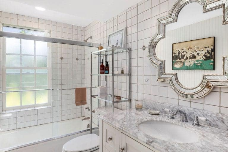 The small white bathroom has a marble countertop and a traditional toilet. It also has a tile wall mounted with wooden sink vanity.