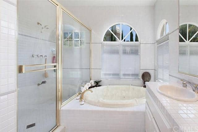 Modern primary bathroom boasts a tiled vanity and walk-in shower accented with gold linings. It includes a deep soaking tub situated beneath the arched windows covered in white blinds.