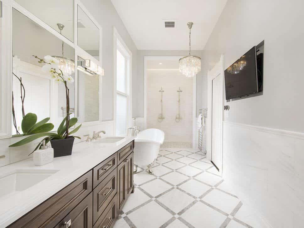 Modern bathroom featuring a freestanding tub and wooden cabinetry on the marble countertops with dual sink lightens by a stunning chandelier. This room also has TV on the white walls.