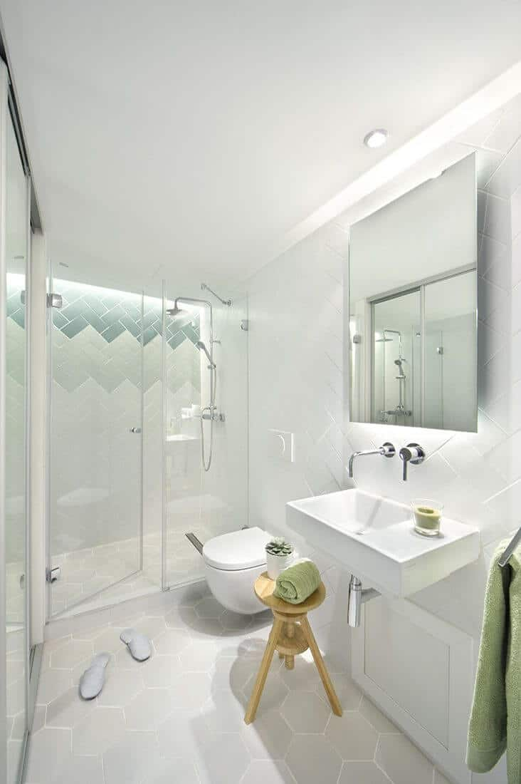 White primary bathroom with a shower area and a small mirror over the basin sink. Modern bathroom with a wall-hung toilet and wooden chair beside.