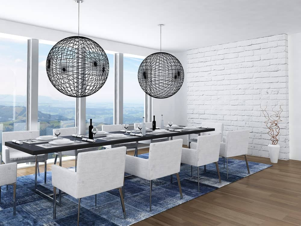 Modern luxury dining room with elegant table setting on the rug. This room features hardwood flooring and white wall with large windows and great view outside.