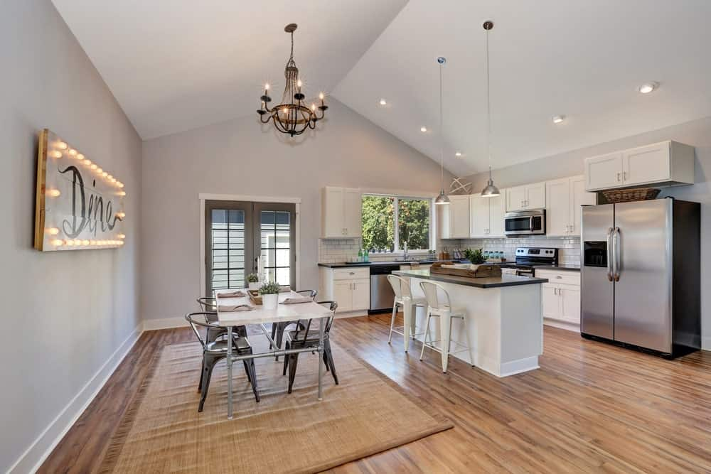 Interior of kitchen and dining room with high vaulted ceiling. White kitchen cabinetry and steel appliances. Antique chandelier above dining table.