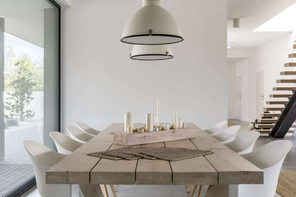 This room features dining wooden table and chairs in modern home with elegant table setting.