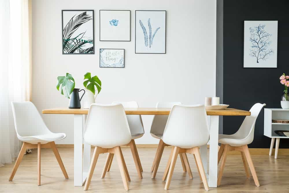 Classic interior of dining room in white walls with great wall decors. This room highlighting a great set of table and chairs.