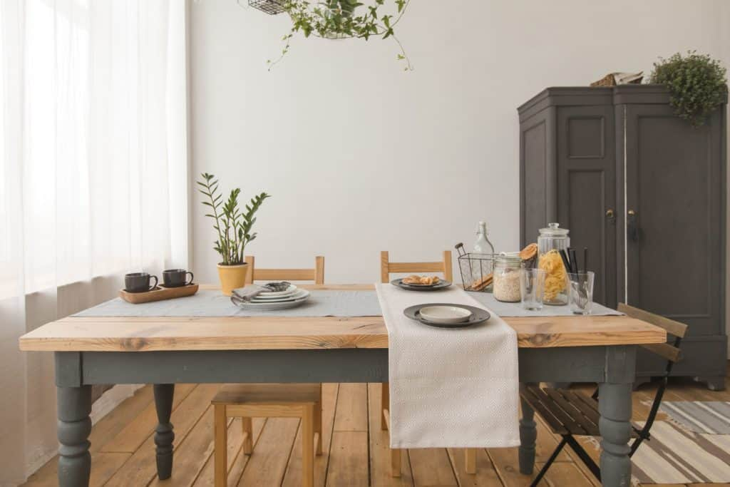 A great dining room featuring hardwood flooring and wooden tables paired with wooden chairs. This room has white walls and large grey cabinet.
