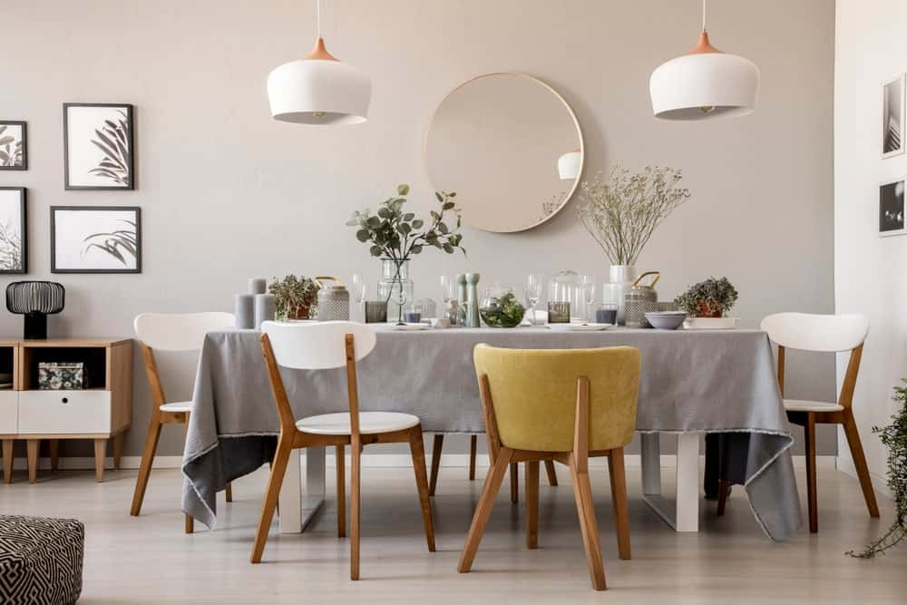 Modern dining area design with spacious wooden chairs at table with tableware. Dining room interior with lamps and round mirror.