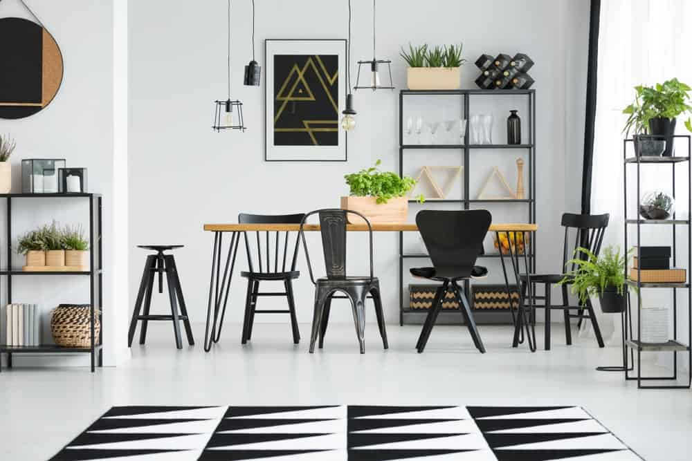 A white dining area highlighting black chairs at table in Scandinavian style dining room with geometric carpet and ferns.