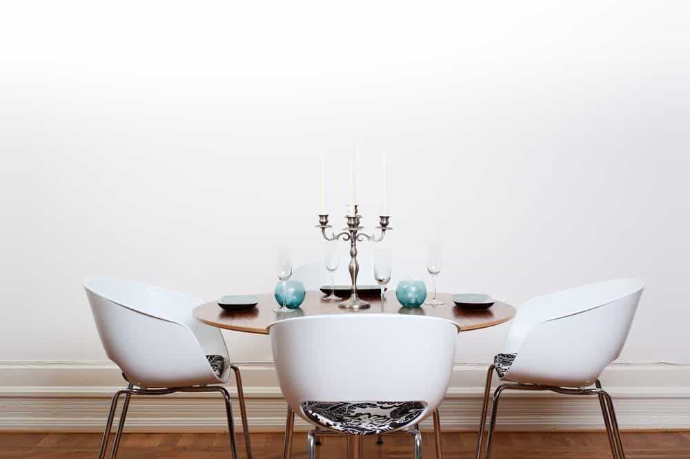 Bright spacious dining room with wooden big table. This room features hardwood flooring and white walls.