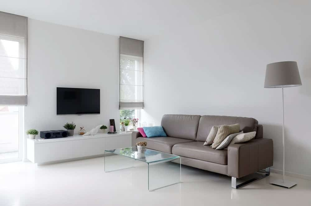 White living room with taupe leather sofa and glass table. This room also has white walls and TV on the wall.