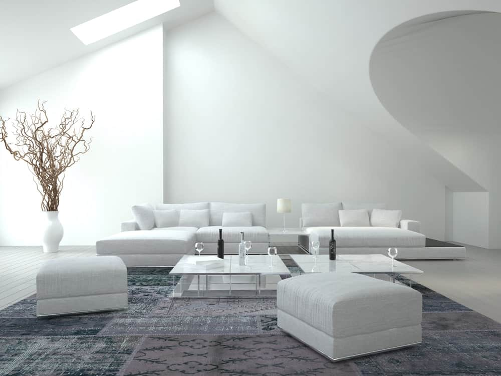White living room featuring modern white sofa set and glass tables on the rug. This room also features a white wall and a high vaulted ceiling.