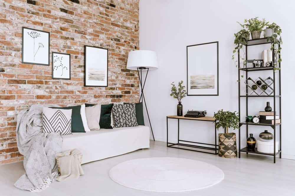 White living room highlighting posters on the red brick wall above white sofa with pillows in bright living room interior with plants.