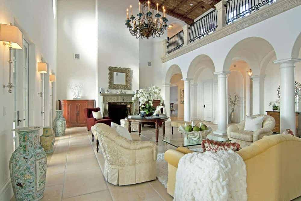 This mansion offers a modern living room with cozy seats and a fireplace set on tiles flooring under the high vaulted ceiling brightens by a stunning chandelier.