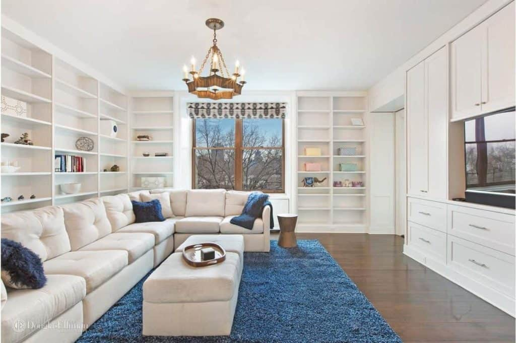 This formal living room is a place where book lovers will enjoy themselves with those multiple bookshelves and cozy sofa set on the blue rug.