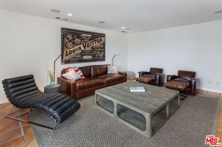 A small living room boasts a brown sofa set and a wooden table on the carpet. This room has a white wall with huge wall decor.