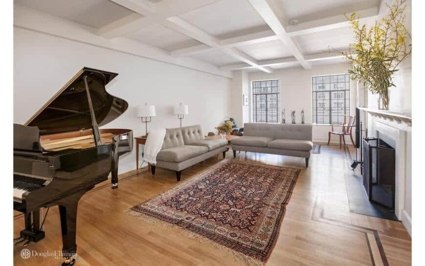Spacious white formal living room featuring an elegant black piano, a cozy sofa set, and a fireplace. This room has hardwood flooring and elegant rug.