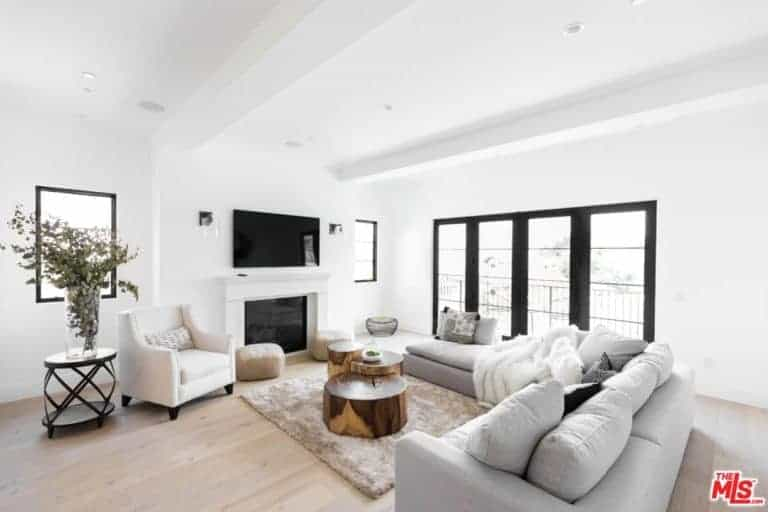 A white formal living room with cozy sofa set and a small table on the rug. This room has a fireplace and a TV on the wall.
