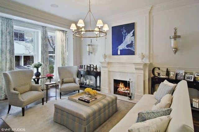 Contemporary living room with flush mount lighting and a stylish rug along with a fireplace and wide glass window. The wall decor adds style to space along with the chandelier.