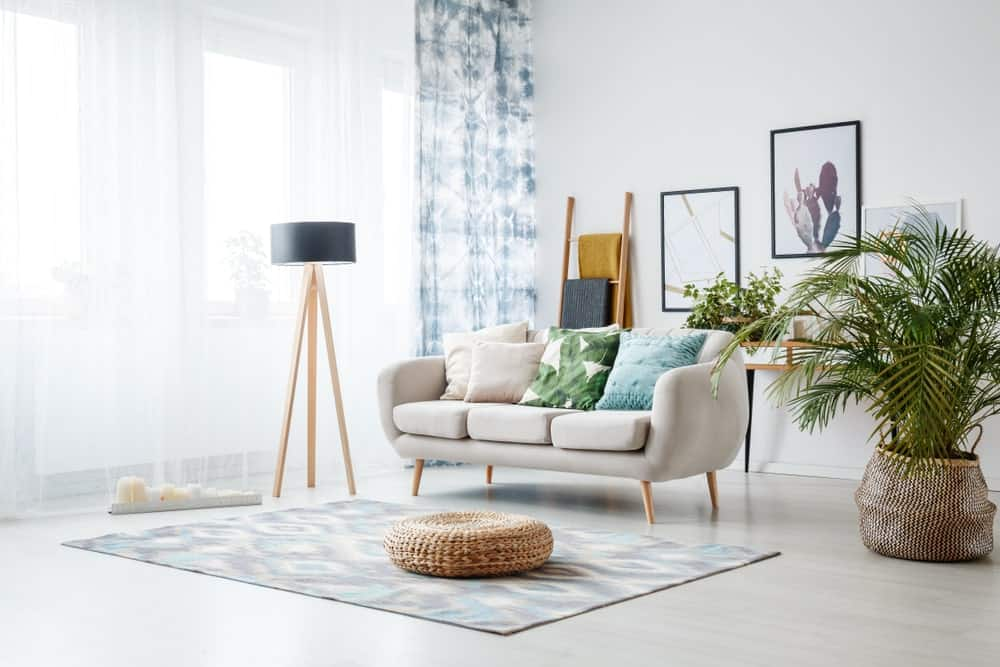 Black lamp standing by a sofa and a row of candles lying on the floor in front of a window shedding light on the interior of boho style living room.