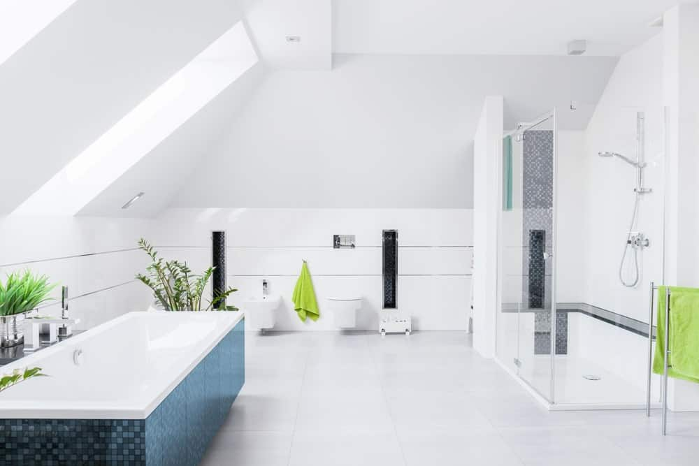 The stylish modern bathroom features a freestanding bathtub that matches the white tiles floorings and wall-hung toilet. This bathroom also features walk-in showers and a high vaulted ceiling.