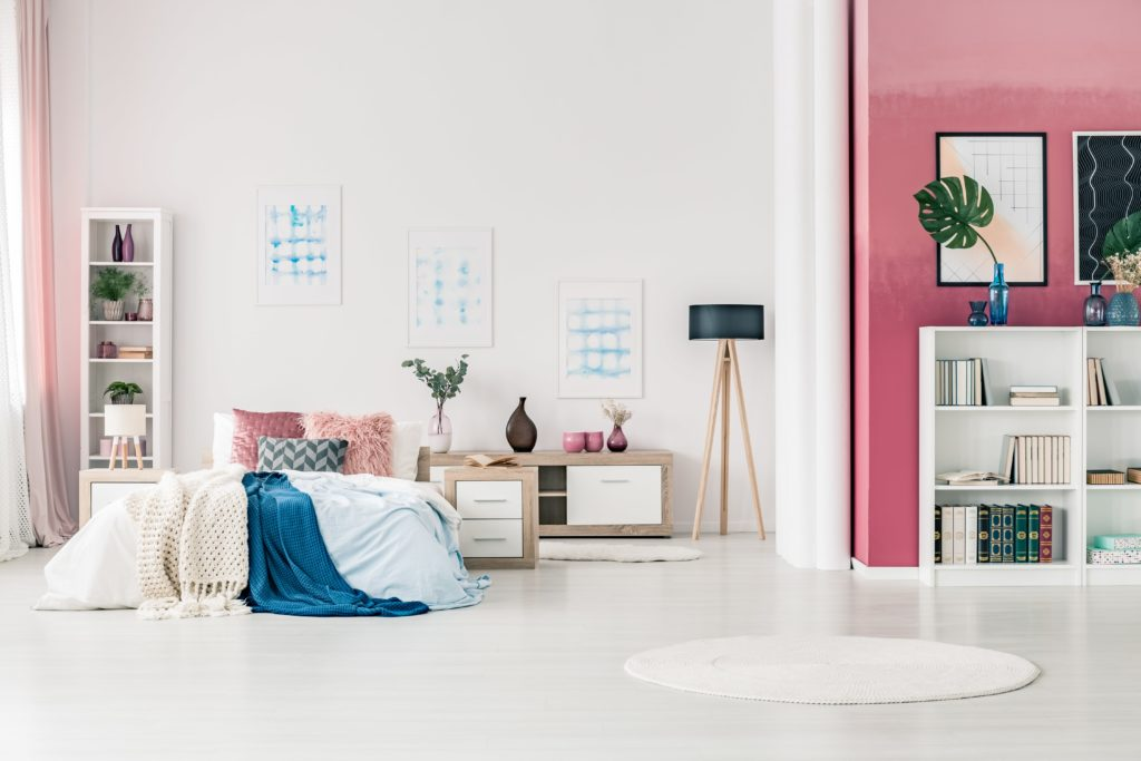 This large white bedroom with comfortable bed in open space bedroom interior with bookcase, modern lamp, round rug, posters, pink and white walls and drapes
