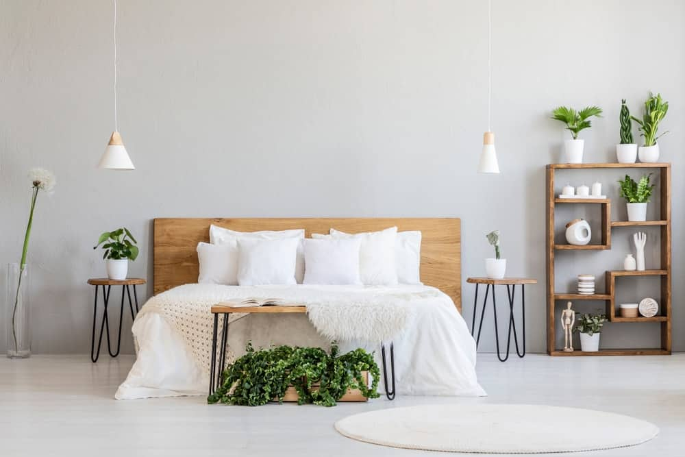 This white master bedroom featuring white pillows on wooden bed in minimal bedroom interior with plants and round rug.