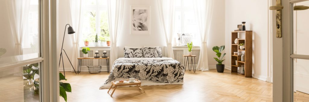 Glass door entrance into a beautiful, bright bedroom interior with breakfast tray on a wooden floor and black floral pattern sheets on a comfy bed.