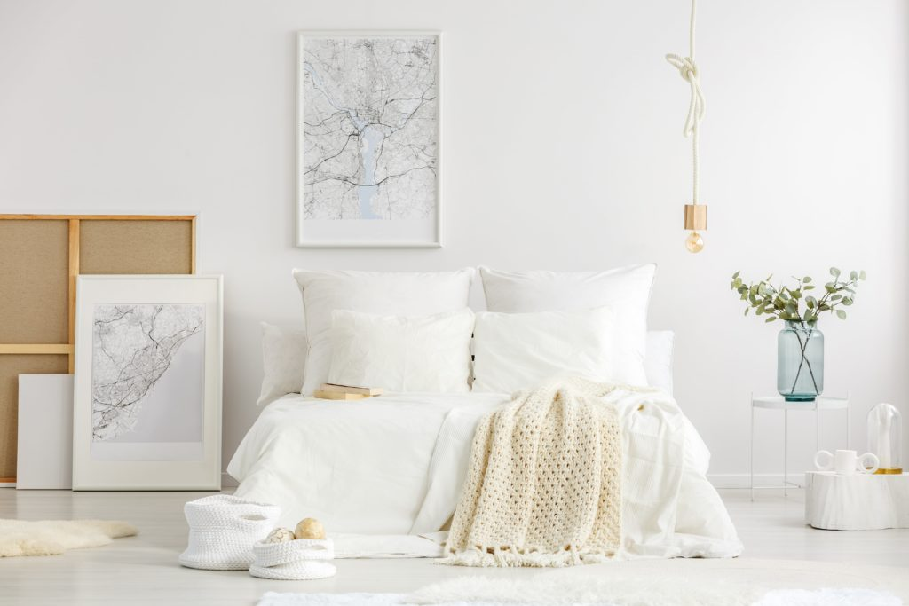 World cities map posters in a white minimalist master bedroom interior with scandinavian design furniture and accessories.