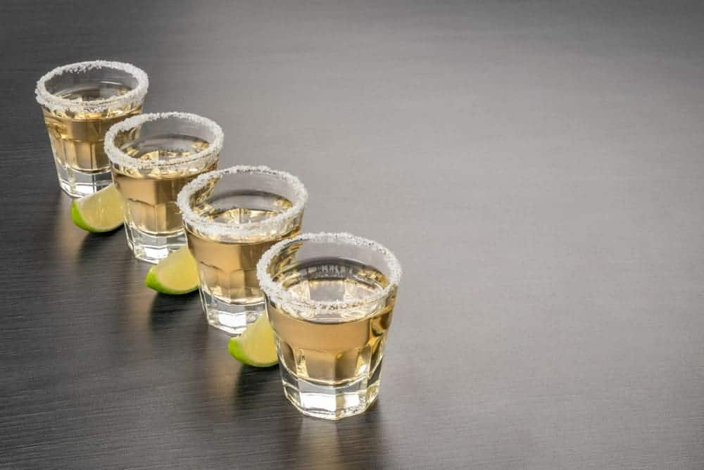 A row of Reposdao Tequila shots with matching lime slices.