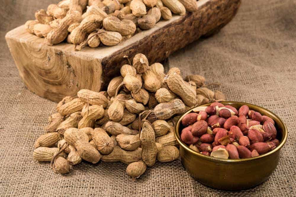 A pile of peanuts with a rustic setting.