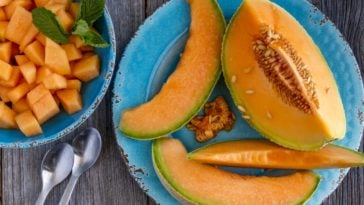 A plate of sliced cantaloupes on a wooden table.