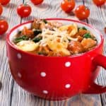 A bowl of creamy spinach and Italian sausage soup with tomatoes on the side.