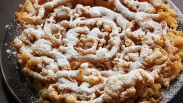 A plate of freshly made funnel cake with powdered sugar on top.