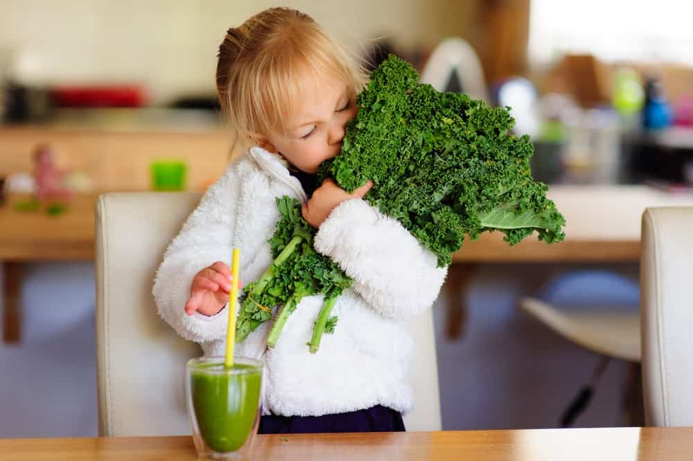 A child carrying a bundle of kale in her arms.