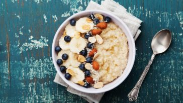 A bowl of healthy porridge that has fruits and nuts.
