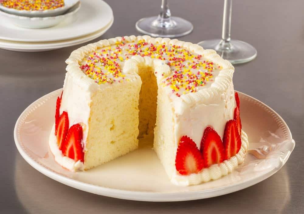 A sliced angel food cake with white frosting and garnish of strawberries and rainbow sprinkles.