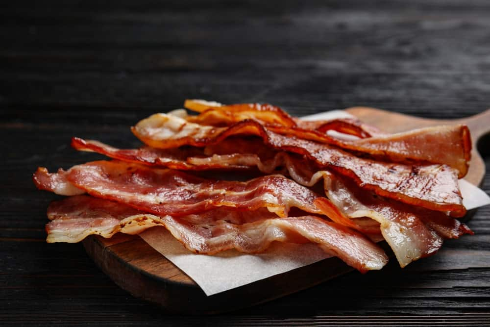 Slices of crispy fried bacon on a chopping board.