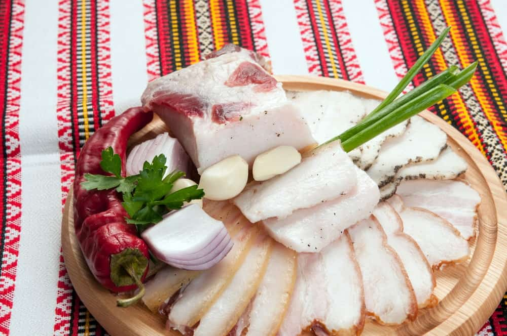 A close look at a spread of traditional Ukrainian salo on a chopping board.