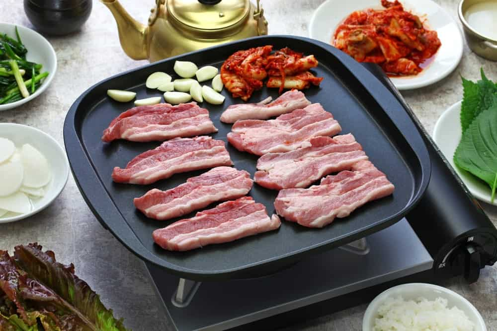 A close look at Korean Samgyeopsal bacon strips on a frying pan with side dishes.