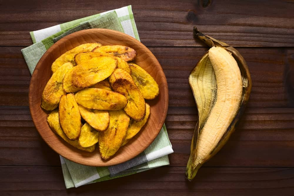 A wooden plate of fried plantains.