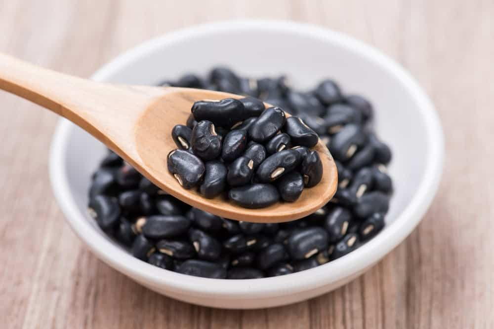 A close look at a bunch of black beans scooped by a wooden spoon.