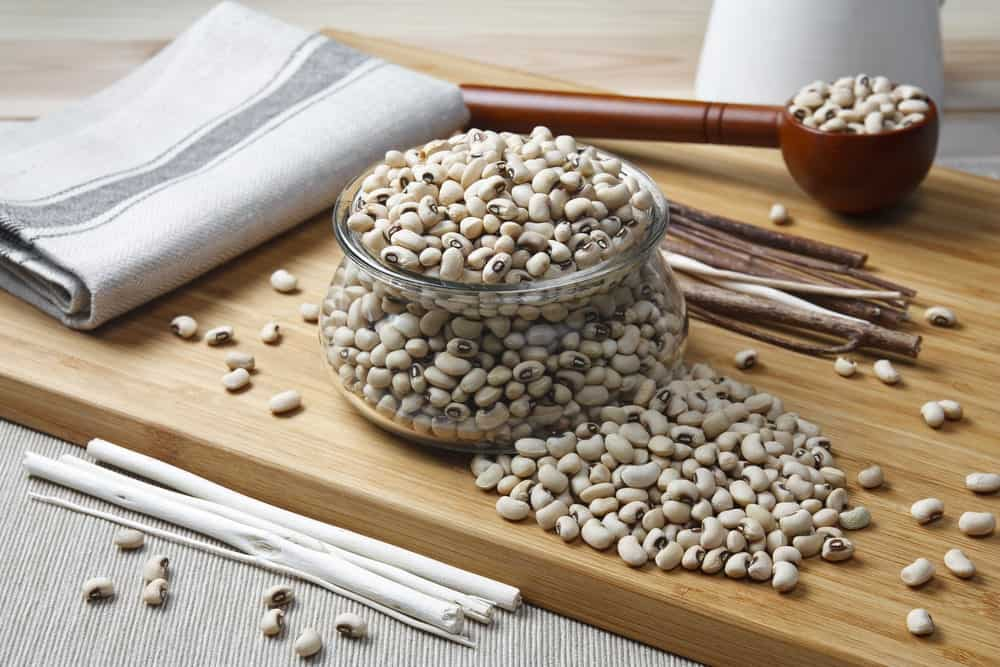 A jar of Navy beans on a chopping board.