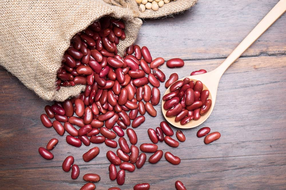 A sack of red beans with a wooden spoon.