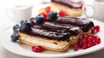 Freshly-made chocolate eclairs with a side of berries.