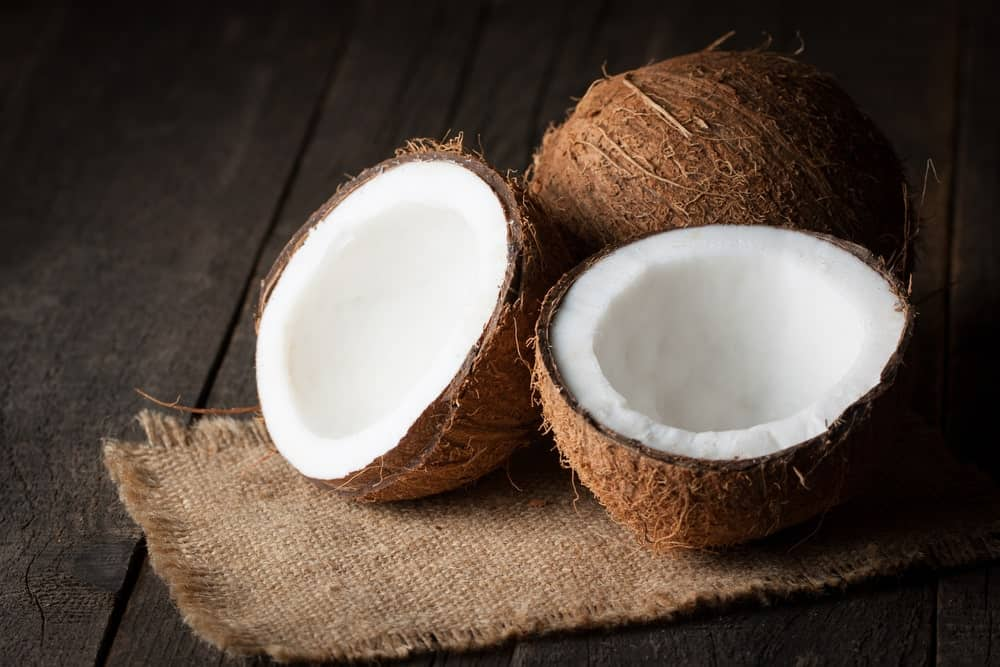Coconut halves on a wooden table.