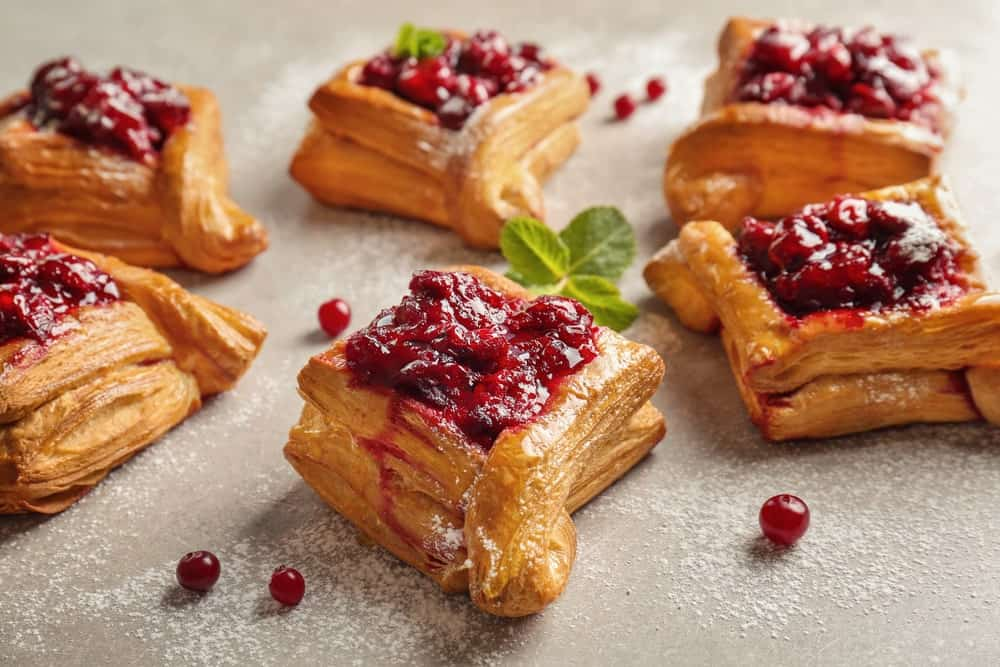 This is a set of freshly-baked puff pastries with berries.
