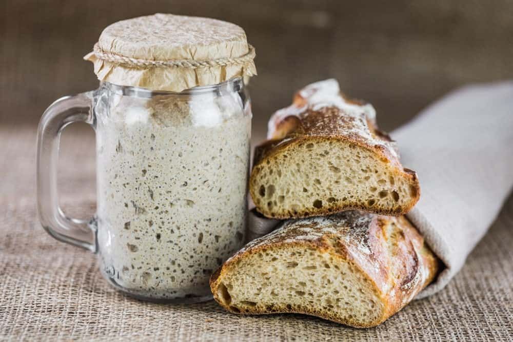 A look at a sourdough starter in a jar next to a baked sourdough bread.