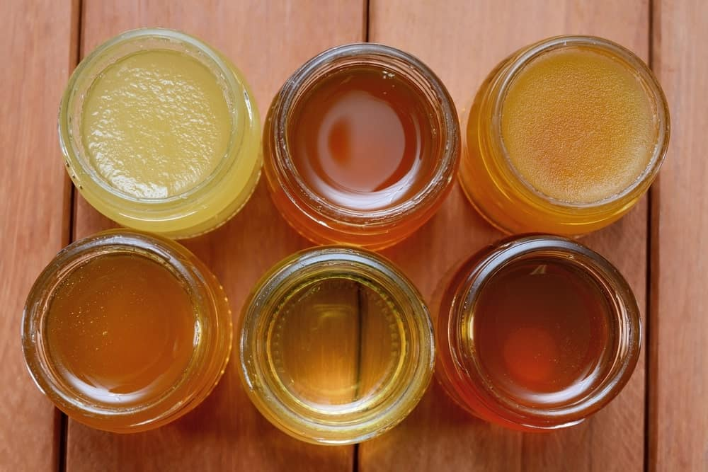Different varieties of honey in separate glass jars.