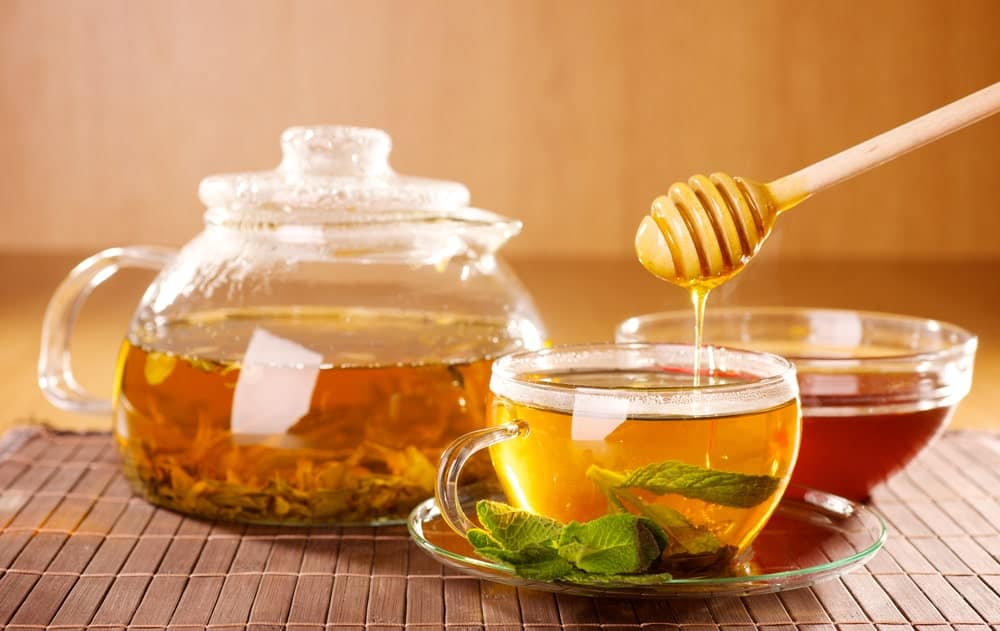 A close look at mint tea being prepared with honey.