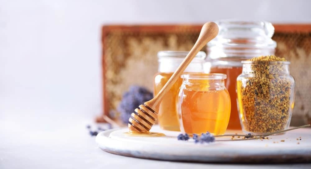 A glass jar of granulated honey along with other types of honey in glass jars.