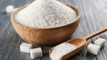 A wooden bowl of sugar along with sugar cubes.